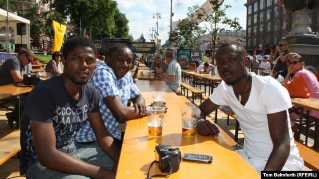 Three Congolese students have a beer in the fan zone in Kyiv. While some longtime residents stay away for fear of violence, visiting fans talk of a welcoming atmosphere.