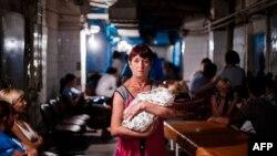 Жанчына трымае немаўля ў бамбасховішчы ў раддоме падчас абстрэлу ў Данецку