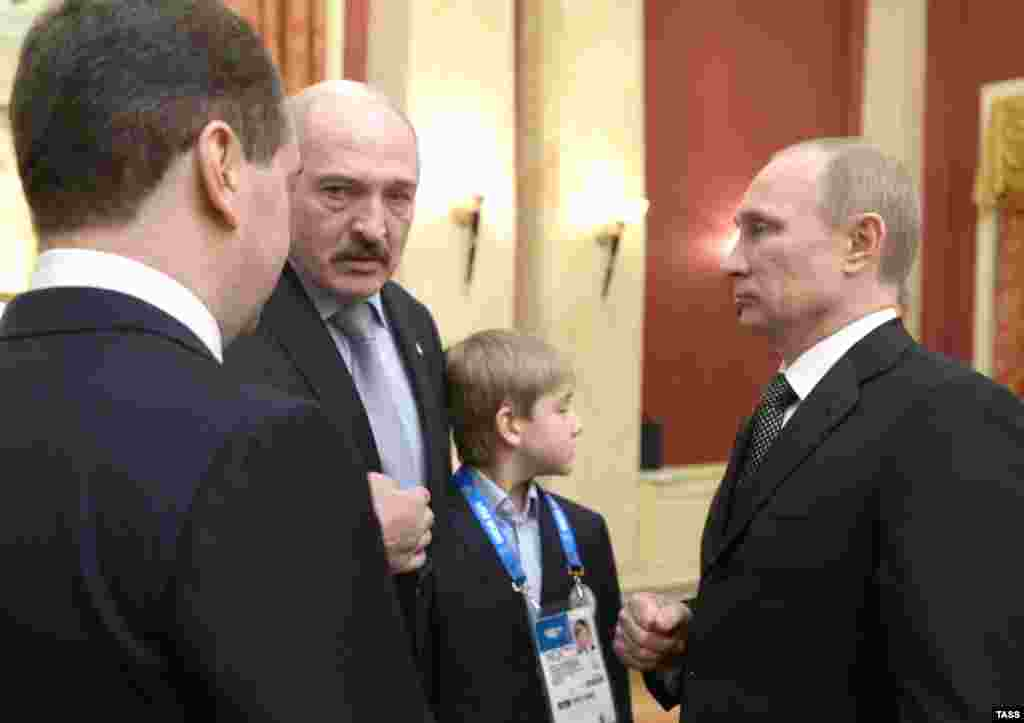 Russian Prime Minister Dmitry Medvedev (left), Lukashenka, Kolya, and Russian President Vladimir Putin chat at a reception for high-profile guests at the Winter Olympics in Sochi in February 2014.