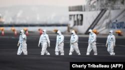 Хора с предпазни маски излизат от круизния кораб, където броят на заразените расте