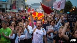 Protesters shout slogans in front of the parliament building in Skopje on April 18.