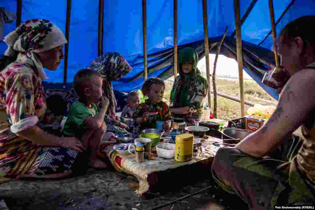 A family gathers in their tent for tea. The Khanty reindeer herders are partly nomadic and move in search of food for their reindeer from spring through autumn.