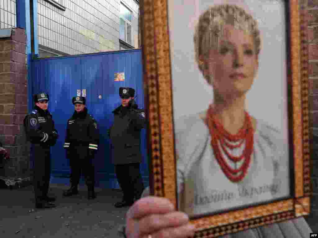 A supporter of Yulia Tymoshenko holds her portrait during a rally in front of the Kyiv prison where the former prime minister is being held. (AFP PHoto/ Sergei Supinsky)
