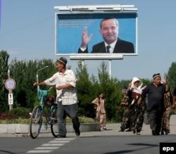 Әндіжан қырғыны жайлы тәуелсіз тергеу жүргізуге рұқсат бермеген Өзбекстанның сол кездегі президенті Ислам Каримовтың суреті бар жарнаманың қасынан өтіп бара жатқан адамдар. Әндіжан, 17 мамыр 2005 жыл.