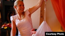 Акушерка взвешивает ребенка после домашних родов