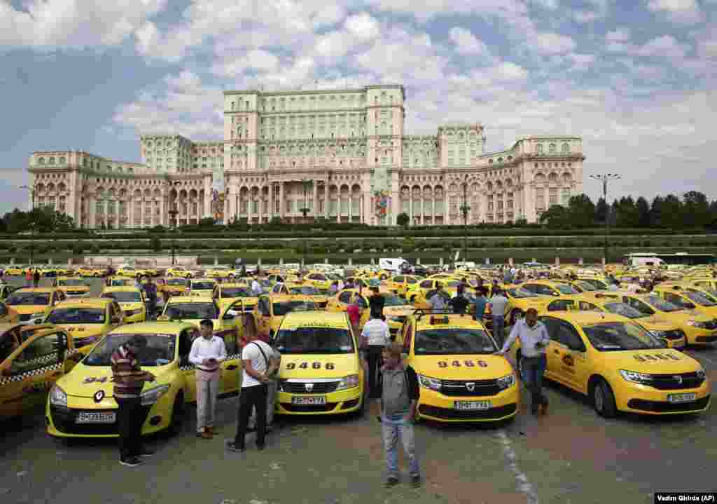 Taxi drivers stage a protest outside the parliament building in Bucharest. Taxi drivers in Romania are protesting against the activities of ride-hailing firms like Uber, Bolt, and Clever and the possibility that legislation being prepared by the government will allow them to function legally. (AP/Vadim Ghirda)