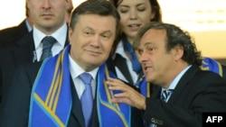Президент УЄФА Мішель Платіні спілкується з Президентом України Віктором Януковичем під час матчу Україна – Швеція, Київ, 11 червня 2012 року