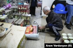 A man toasts bread on a heater in a store in Stepanakert.