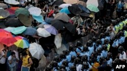 China/Hong Kong -- Pro-democracy protesters hold umbrellas and wear protective clothing in front of a police line near the government headquarters in Hong Kong on September 28, 2014