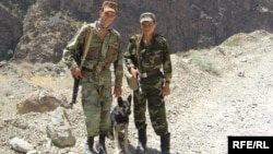Doi membri ai trupelor de pază de la frontiera tadjică, cu câine, la granița cu Afganistanul