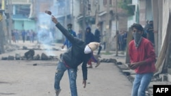 FILE: A Kashmiri protestor throws a stone towards Indian government forces during clashes in Srinagar.