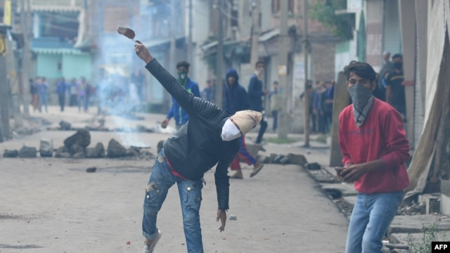 India - A Kashmiri protestor throws a stone towards Indian government forces during clashes in Srinagar on August 29, 2016