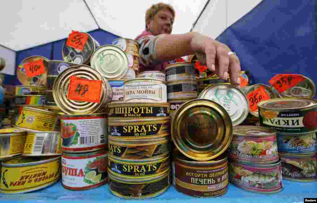 """Продавец предлагает консервы на агропромышленной выставке """"Агрорус"""" в Санкт-Петербурге"""