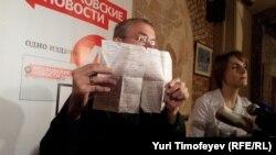 Олег Шеин на брифинге в Москве показывает медицинскую справку, подтверждающую факт голодовки