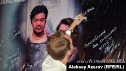 """Зритель фильма """"Глина - любовь"""" пишет на баннере фильма пожелания. Алматы, 17 мая 2017 года."""