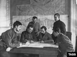 Большевистское военное руководство «обсуждает подавление Кронштадтского восстания». На заднем плане — карта острова-крепости.