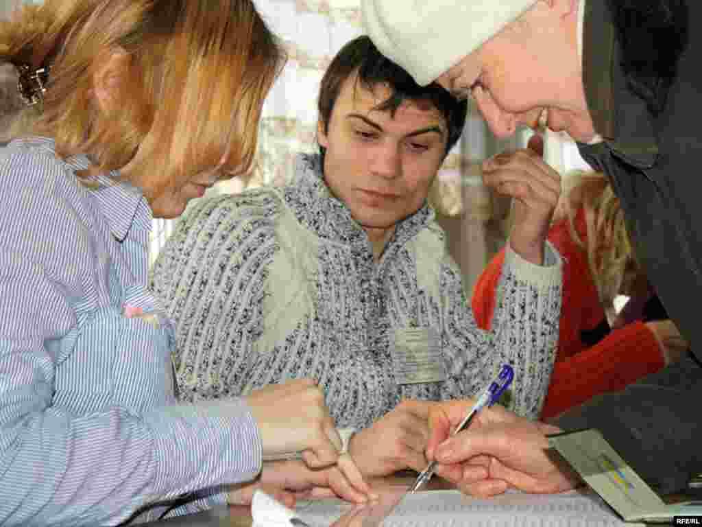 Жінка розписується в отриманні бюлетеня, Київ