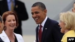 U.S. President Barack Obama (center) is greeted by Australian Prime Minister Julia Gillard (left) upon his arrival in Canberra on November 16.