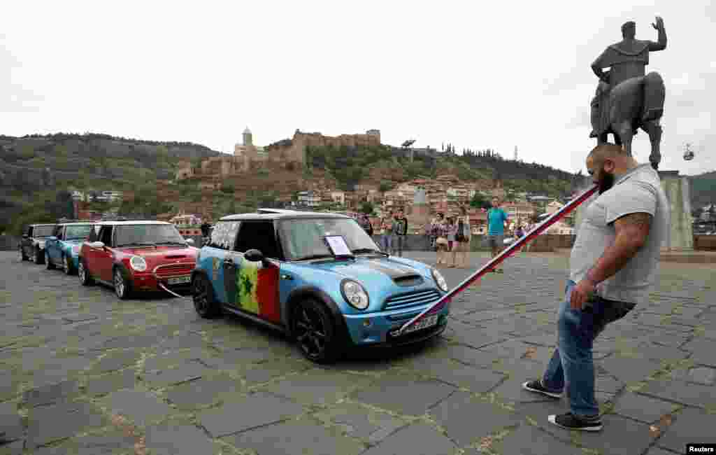 Guram Ustiashvili pulls four cars with his teeth during an attempt to set a world record in Tbilisi, Georgia. (Reuters/David Mdzinarishvili)