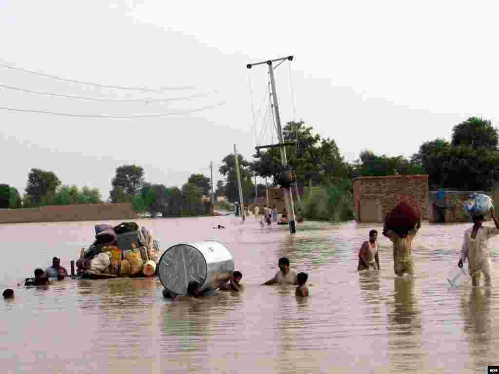 Люди покидают затопленные деревни в Дера-Исмаилхане, 1 августа 2010