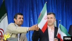 Ahmadinejad (left) handing an Iran flag to Mashaei, his vice president, in Semnan, Iran, on April 11, 2013.