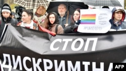 "A woman holds a placard reading ""Stop discrimination"" as she takes part in a rally of Ukrainian activists and representatives of the lesbian, gay, bisexual, and transgender community in front of parliament in Kyiv in November 2015."
