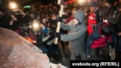 Удзельнік Майдану спрабуе раскалоць павалены помнік.