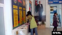 Two women push a pile of ballots into the ballot box in Baku