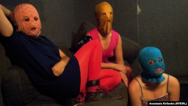 The three Pussy Riot members gathered in a darkened studio, with all three wearing the brightly colored stockings and the group's requisite balaclavas in gold, orange, and blue.