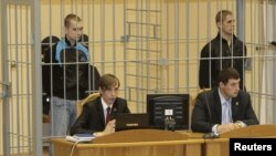 Dzmitry Kanavalau (left) and Ulad Kavalyou are seen in the defendants' cage before court hearings in Minsk on September 15, 2011.