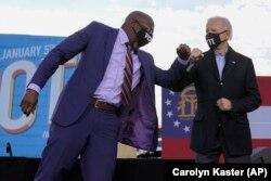 Joe Biden megválasztott elnök könyökpacsit ad Raphael Wanock szenátorjelöltnek Atlantában, 2021. január 4-én. Joe Biden Warncokkal és a másik demokrata jelölttel, Jon Ossoff-fal vet közösen részt egy kampányeseményen.