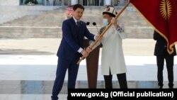 Председатель кабмина Улукбек Марипов вручает флаг Кыргызстана капитану олимпийской сборной Атабеку Азисбекову. 13 июля 2021 года.