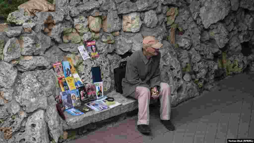 Літній чоловік продає книги і брошури