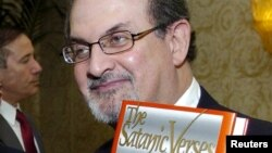 "Author Salman Rushdie (R) poses with his 1988 book ""The Satanic Verses"" in the U.S. File photo"