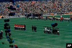 The teams for the Soviet Union (left, in red) and Mexico (right, in green) pause before the kickoff of their group stage match in the 1970 World Cup at Estadio Azteca in Mexico City on May 31, 1970. The match ended in a 0-0 draw.