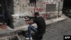 Syria -- A Syrian rebel takes position on a street in the northern city of Aleppo, 03Aug2012