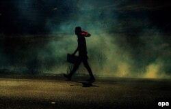 Палестинец, протестующий у одного из КПП против военной операции Израиля, убегает, спасаясь от слезоточивого газа, который против митингующих использовали израильские военные