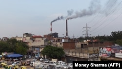 Smoke billows from two smokestacks at the coal-based Badarpur Thermal Station in New Delhi.