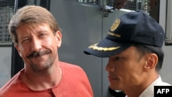 Alleged Russian arms dealer Viktor Bout is escorted by police as he arrives for a hearing at the Criminal Court in Bangkok on August 20.