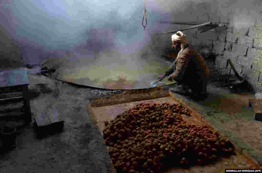 Owganystanayň Nangarhar welaýatynyň Kama etrabyndaky gadymy fabrikde şeker gamşynyň toşabyndan goňur şeker öndürýän işçi. (AFP/Noorullah Shirzada)