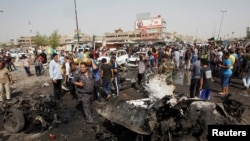 Iraqi security forces and onlookers gather at the site of a car bomb attack in Baghdad's mainly Shi'ite district of Sadr City on May 17.