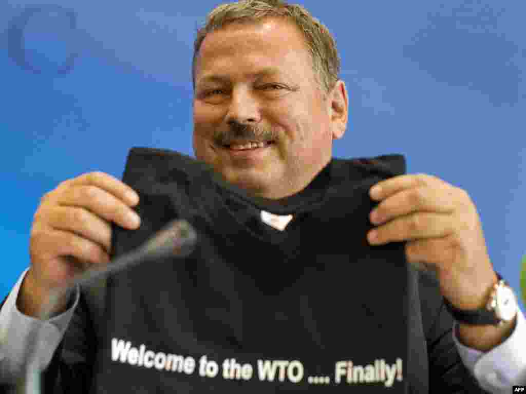Russian chief negotiator Maxim Medvedkov smiles with a T-shirt he received after formal negotiations on Russia's membership bid to join the World Trade Organization in Geneva. (Photo for AFP by Fabrice Coffrini)