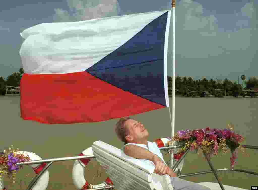 Sitting beneath the Czech flag, Havel enjoys the sun on a boat travelling to Bangkok while on a visit to Thailand in 1994. (Igor Zehl)