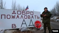 Донбастағы ресейшіл сепаратистер тосқауыл бекетінде тұрған қаруыл адам. Желтоқсан, 2014 жыл.