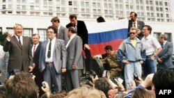 Boris Yeltsin (far left) standing atop an armored vehicle during the heady days of August 1991.