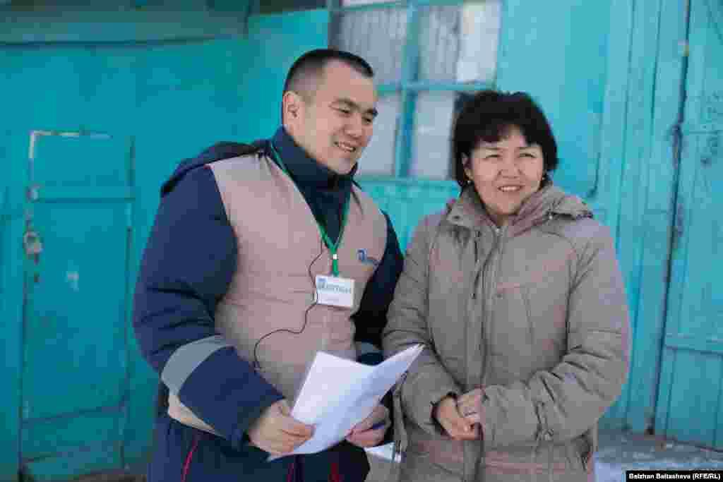 Салтанат Куатова, мать троих детей, стоит рядом с волонтером. Семья живет на то, что муж зарабатывает таксистом в Алматы.