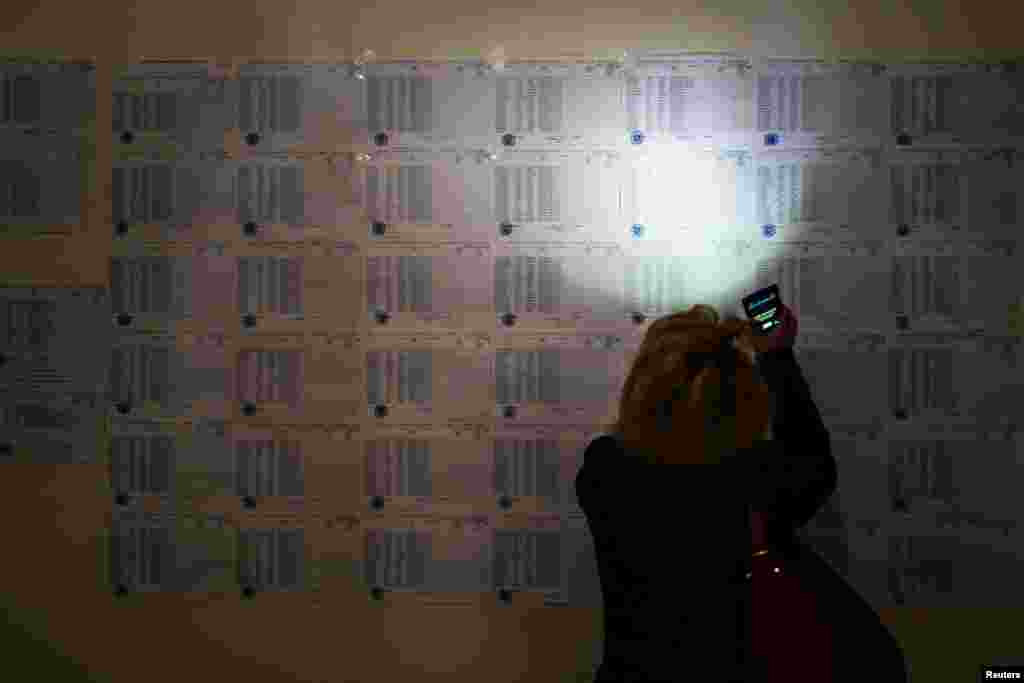 A woman uses her mobile phone to read a voters list during parliamentary elections at a poling station in Yerevan on April 2. (Reuters/Vahan Stepanyan/PAN Photo)