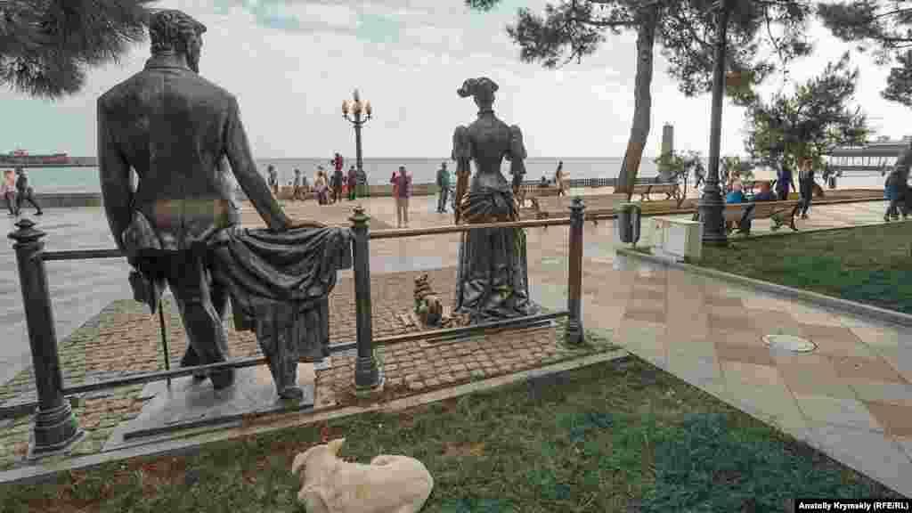 Дворняга за бронзовой скульптурной композицией «Дама с собачкой»