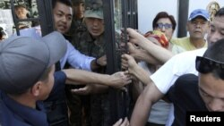 Activists block an entrance to the seat of the Kyrgyz parliament during a protest rally in Bishkek on August 15 over the treatment of former Defense Minister Vaktybek Kalyev.