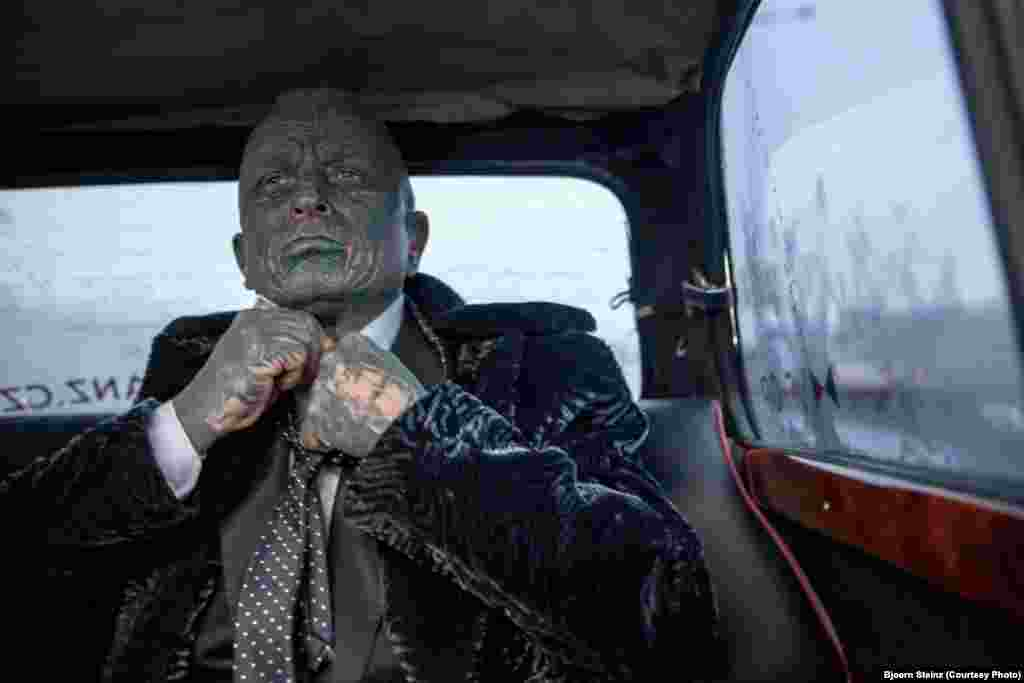 """Vladimir Franz, a candidate for the Czech presidency, corrects his tie while riding in """"Air Franz One,"""" his official campaign car, in Prague. Franz is a prominent Czech composer, painter, and professor who is also a registered candidate in the 2013 Czech presidential election on January 11-12. He is a polling a surprising third in opinion surveys."""